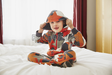 young boy sitting on bed wearing