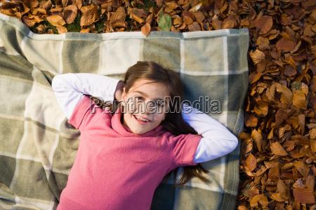 girl lying on leaves