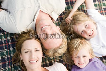 family lying on blanket
