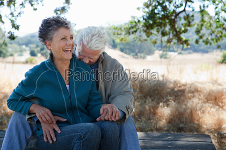 happy couple sitting on picnic table