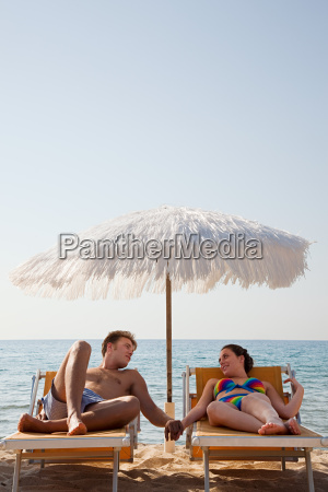 young couple on sun loungers holding