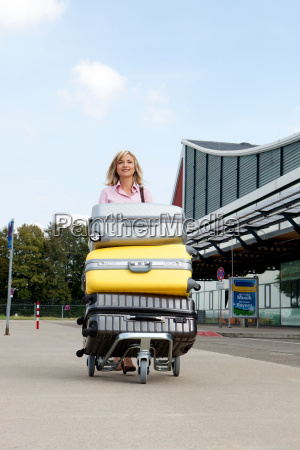 mid adult woman pushing luggage trolley
