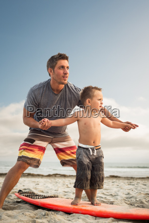 young man teaching son to surf