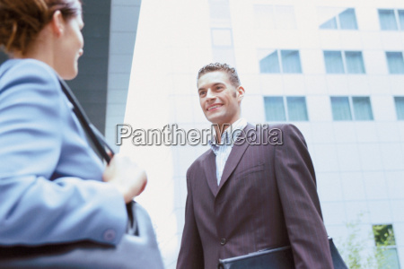 businessman and businesswoman talking outside office