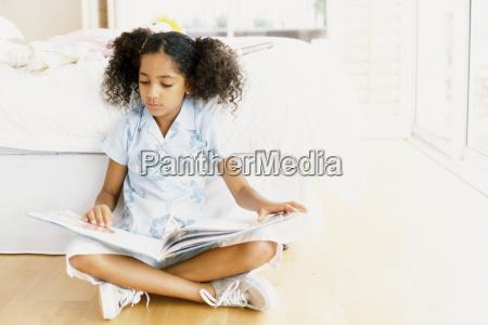 girl reading against bed