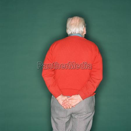 senior man holding his hand behind