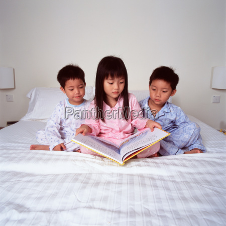 children on bed reading book