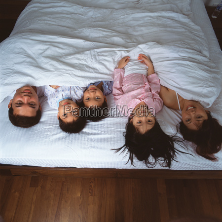 young family lying in bed