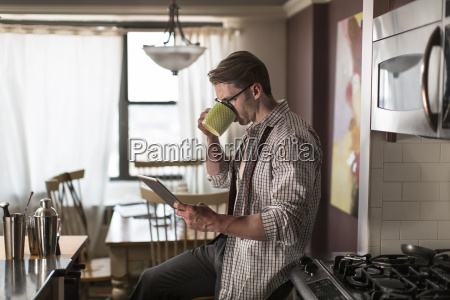 mid adult man in kitchen drinking