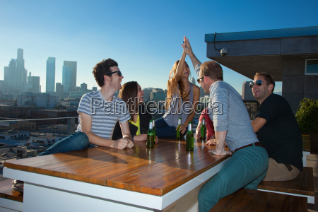 six adult friends drinking beer at