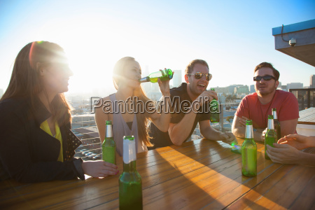 four adult friends drinking beer at