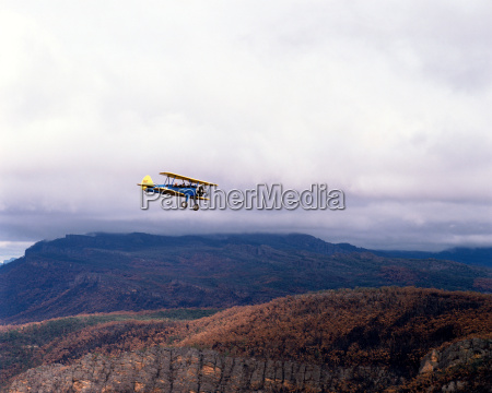 biplane with mountains in the background