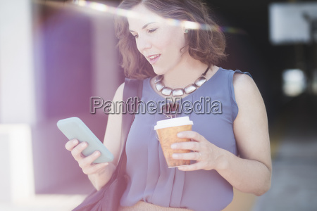 mid adult woman outdoors using smartphone