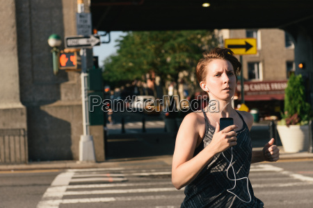mid adult woman running wearing earphones