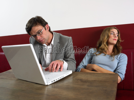 woman bored as man works on