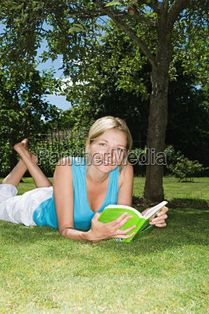 woman lying on the grass reading