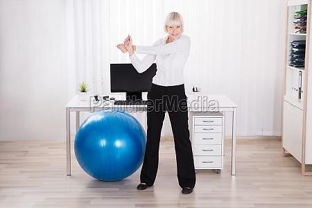 forretningskvinde gor motion pa kontoret