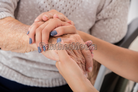 female doctor holding hand of senior