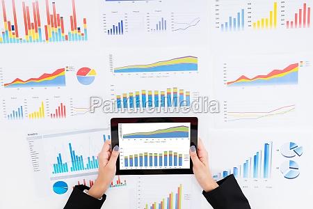 forretningskvinde analysere finansielle grafer brug digital