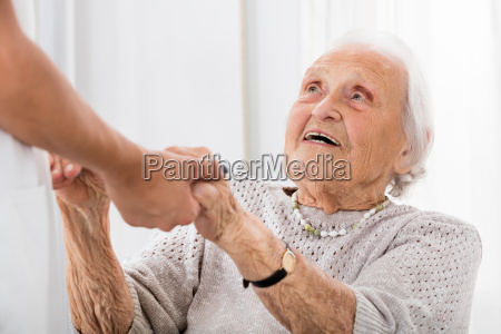 senior patient holding hands of female