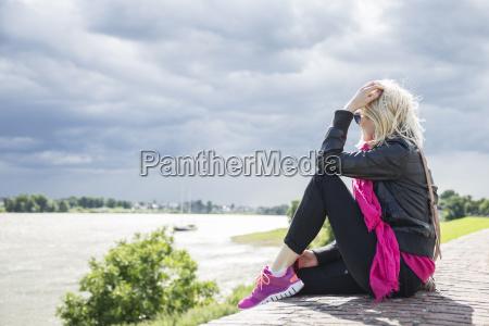 kvinde der sidder pa vaeggen rhinen