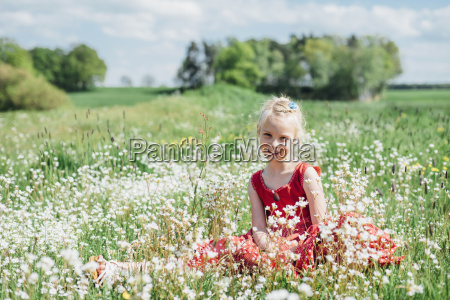 smiling girl sitting in meadow
