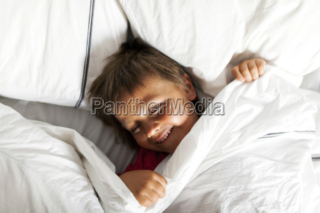 smiling little boy lying in bed