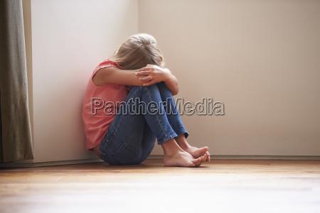 ulykkelig barn sidder pa gulvet i