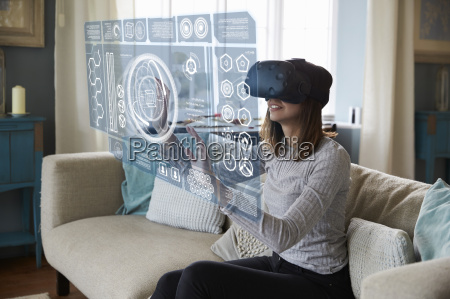 woman sits on sofa at home