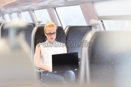 kvinde rejser med tog arbejder pa