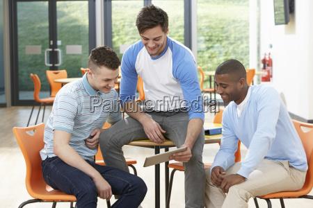 tre mandlige studerende ser pa digital