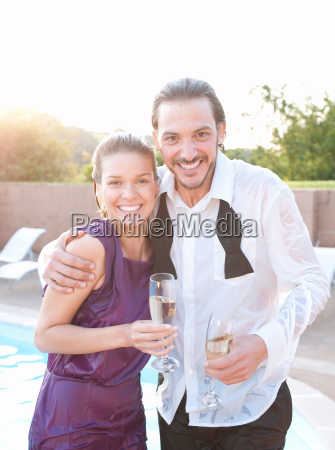 couple wet by swimming pool dressed
