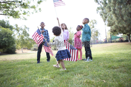 children holding up american flags in