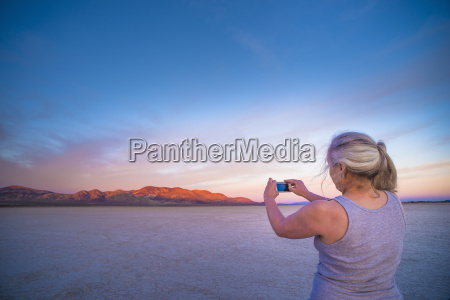 woman taking smartphone photograph of salt