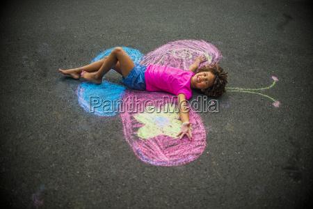 young girl lying on floor between