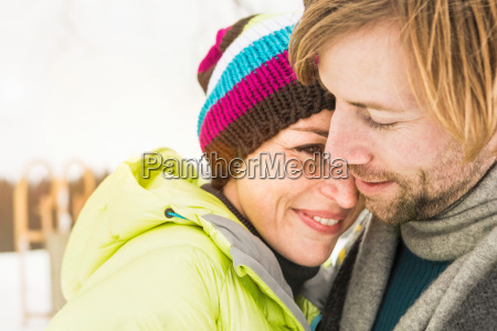 mid adult couple embracing woman wearing