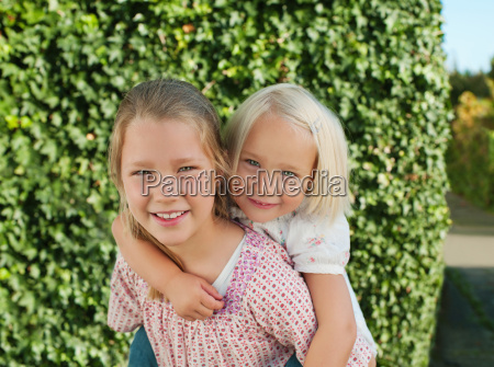 girl carried by sister on back