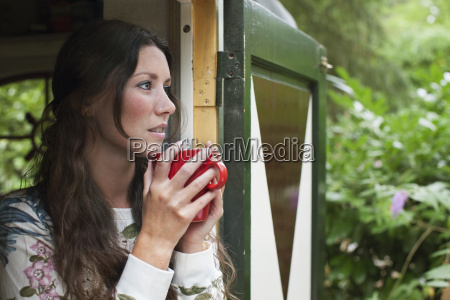 young woman drinking coffee in cabin