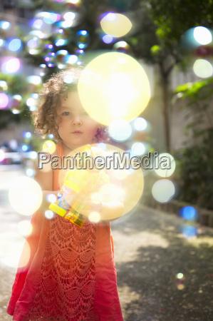 girl wearing dress using bubble gun