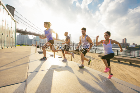 four young adult running friends running