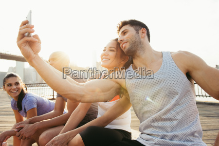 young adult running couple taking smartphone