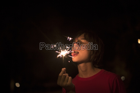 portrait of boy holding sparkler on