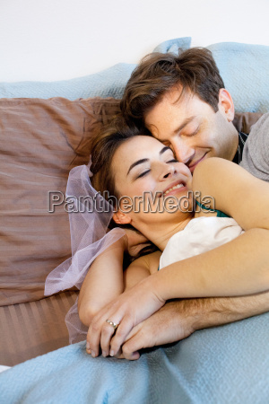 young newlywed couple lying in bed