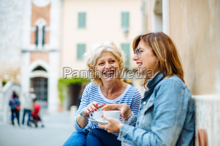 two mature female friends talking and