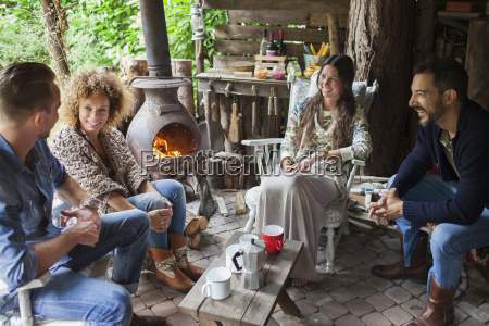four adult friends drinking coffee in