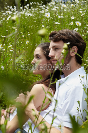 couple relaxing in field of flowers