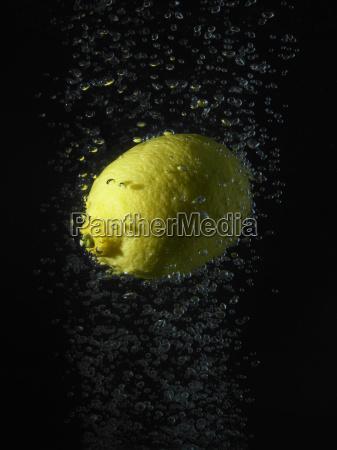 lemon in bubbles black background
