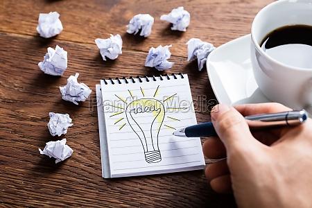person tegning lyspaere pa notesblok