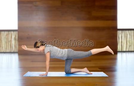 kvinde gor yoga i balancering bord