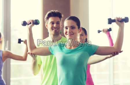 happy women and trainer with dumbbells